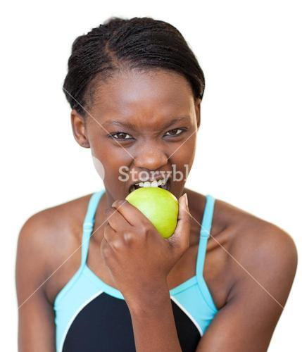 Cheerful fitness woman eating an apple