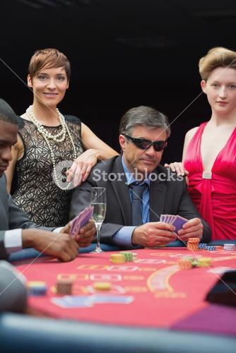 Man in sunglasses smiling at poker table