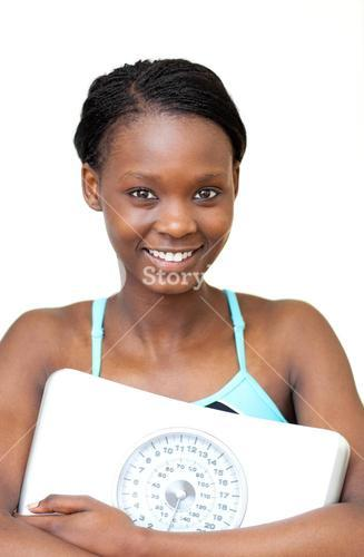 Happy fitness woman holding a weight scale
