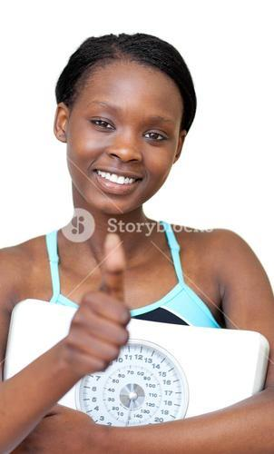 Charming fitness woman with thumb up holding a weight scale