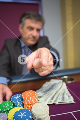 Man with chips and cash pointing