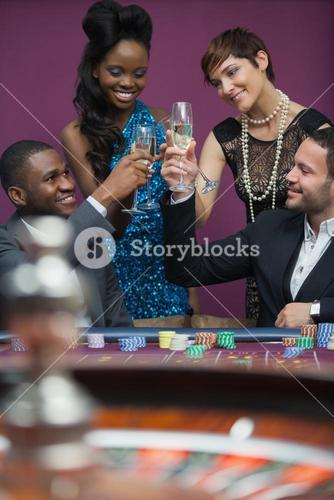 People clinking glasses at roulette table