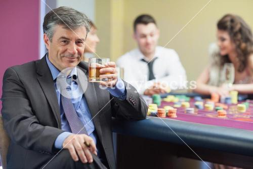 Man drinking whiskey at roulette table