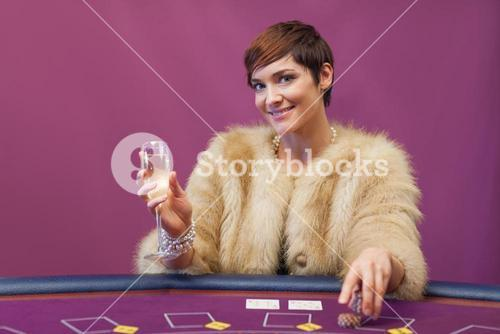 Woman with champagne at poker table