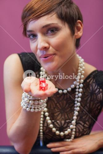 Woman holding and blowing on dice for luck