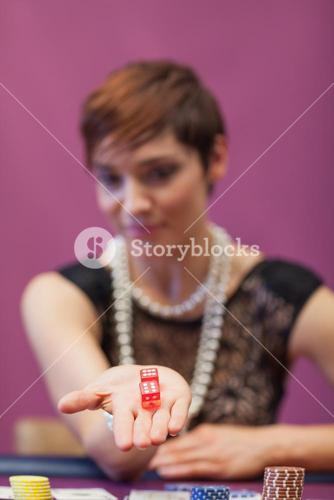 Woman at table holding dices