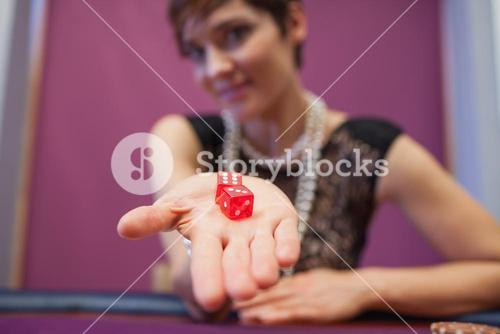 Woman holding dices at table
