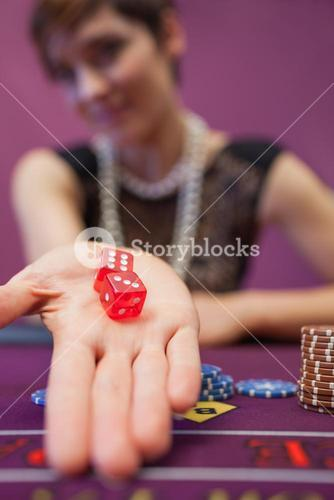 Woman sitting at table while holding dices