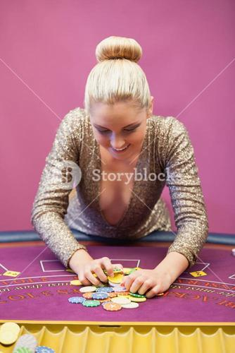 Woman in a casino grabbing chips