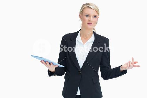 Woman wondering while holding tablet