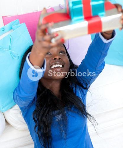 Happy woman holding a present sitting on the floor