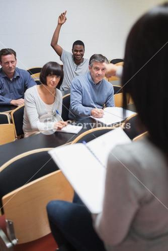 Smiling man asking question in lecture