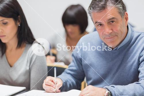Man taking notes in a lecture