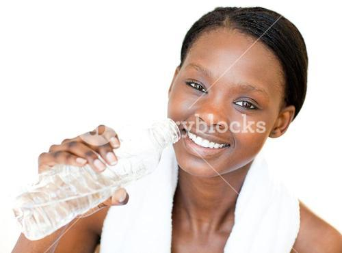 Happy fitness woman drinking water