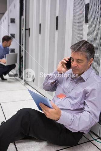 Technician on the phone doing server maintenance with tablet pc