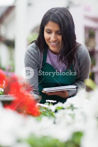 Worker looking at the flowers and making notes