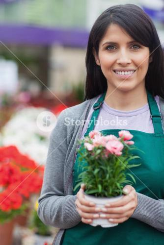 Garden center worker holding a potted flower and smiling
