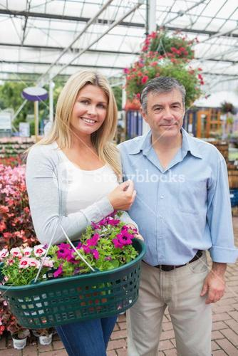Couple holding a basket of plants and flowers