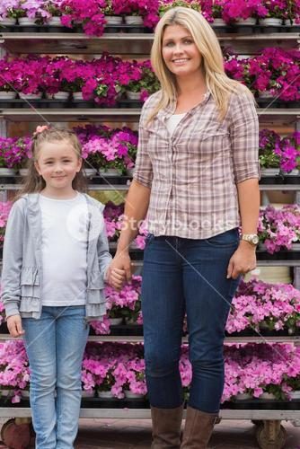 Mother and daughter holding hands in garden center