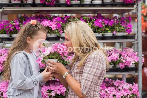 Mother and daughter smelling plant