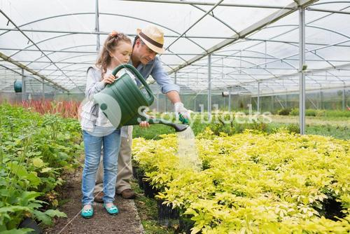 Gardener and granddaughter watering the plants