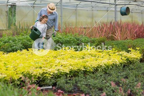 Grandfather and child watering plants