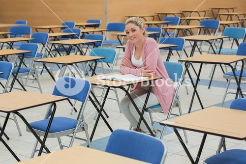 Student sitting at desk in empty exam hall