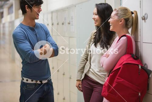 Friends talking in college hallway
