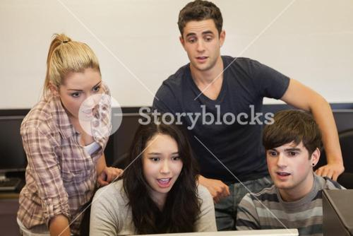 Students sitting at the computer looking shocked