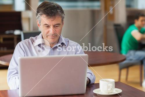 Man in a coffee shop working on the laptop