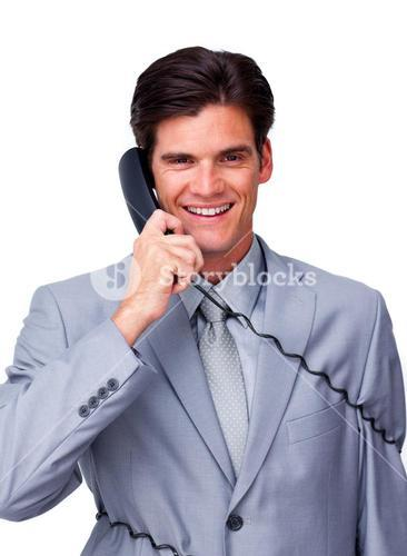 Smiling male executive tangle up in phone wires