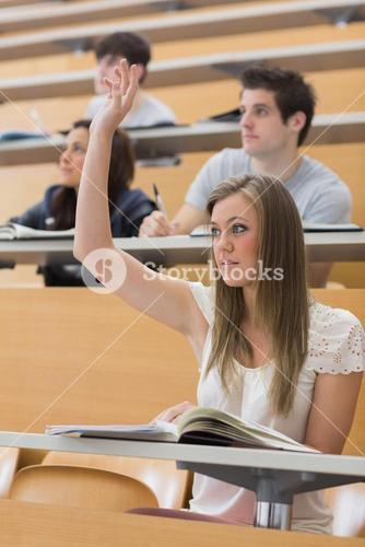 Woman sitting at the lecture hall with hand up