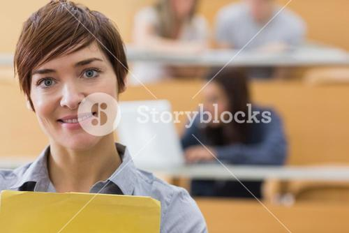Teacher standing at the lecture hall smiling