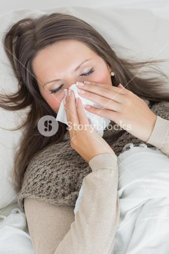 Woman lying on sofa and blowing nose