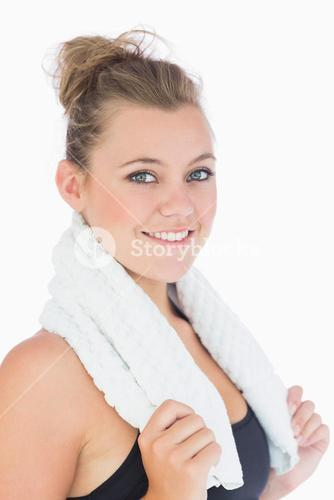 Woman standing and smiling with towel over shoulders