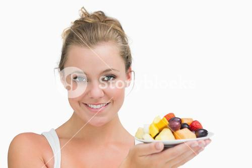 Woman holding up a plate fruits