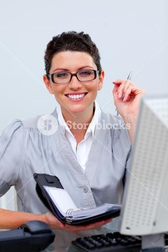 Attractive business woman writting on her agenda