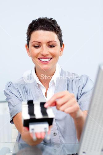 Brunette businesswoman consulting a business card holder