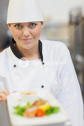 Smiling chef behind dinner plate