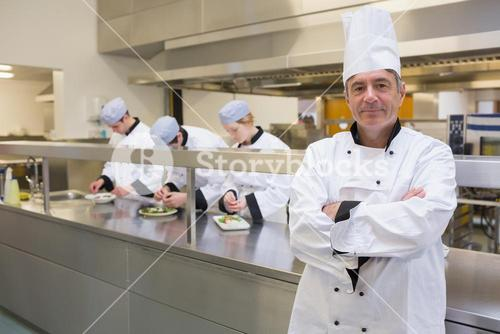 Head chef smiling in busy kitchen
