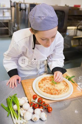 Chef finishing off a pizza