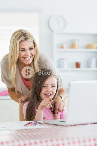Mother and child laughing at laptop with child pointing