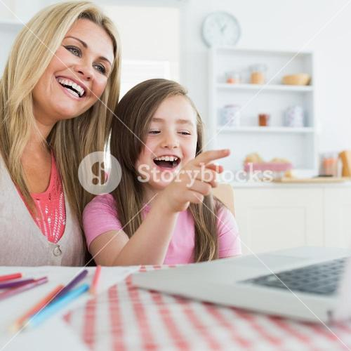 Mother and daughter laughing at laptop