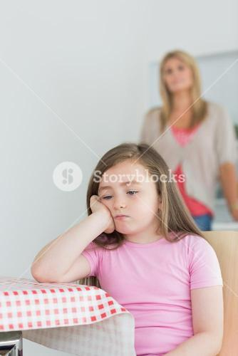 Little girl sitting looking exasperated
