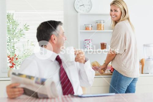 Couple standing and sitting at the kitchen smiling before work