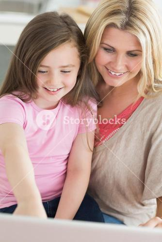 Mum and child sitting and smiling at laptop