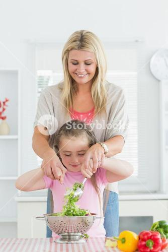Woman and child mixing salad together