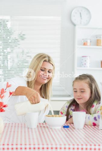 Mother pouring milk into cereal bowl for daughter