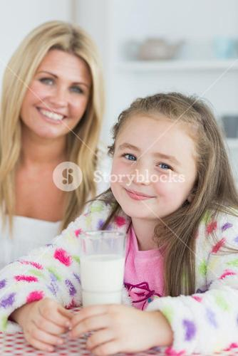 Little girl drinking a glass of milk with her mum