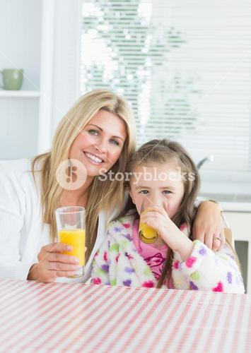 Woman and Child sitting at the kitchen table holding a glass of juice